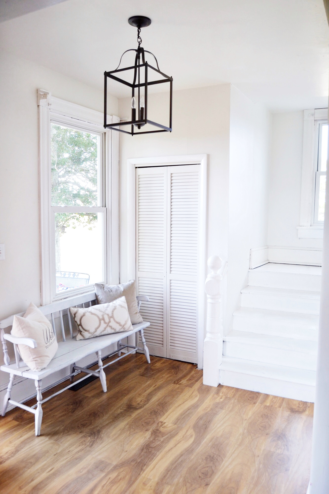 Farmhouse entryweay, white painted stairs, black lantern - The Morris Manor Home Tour