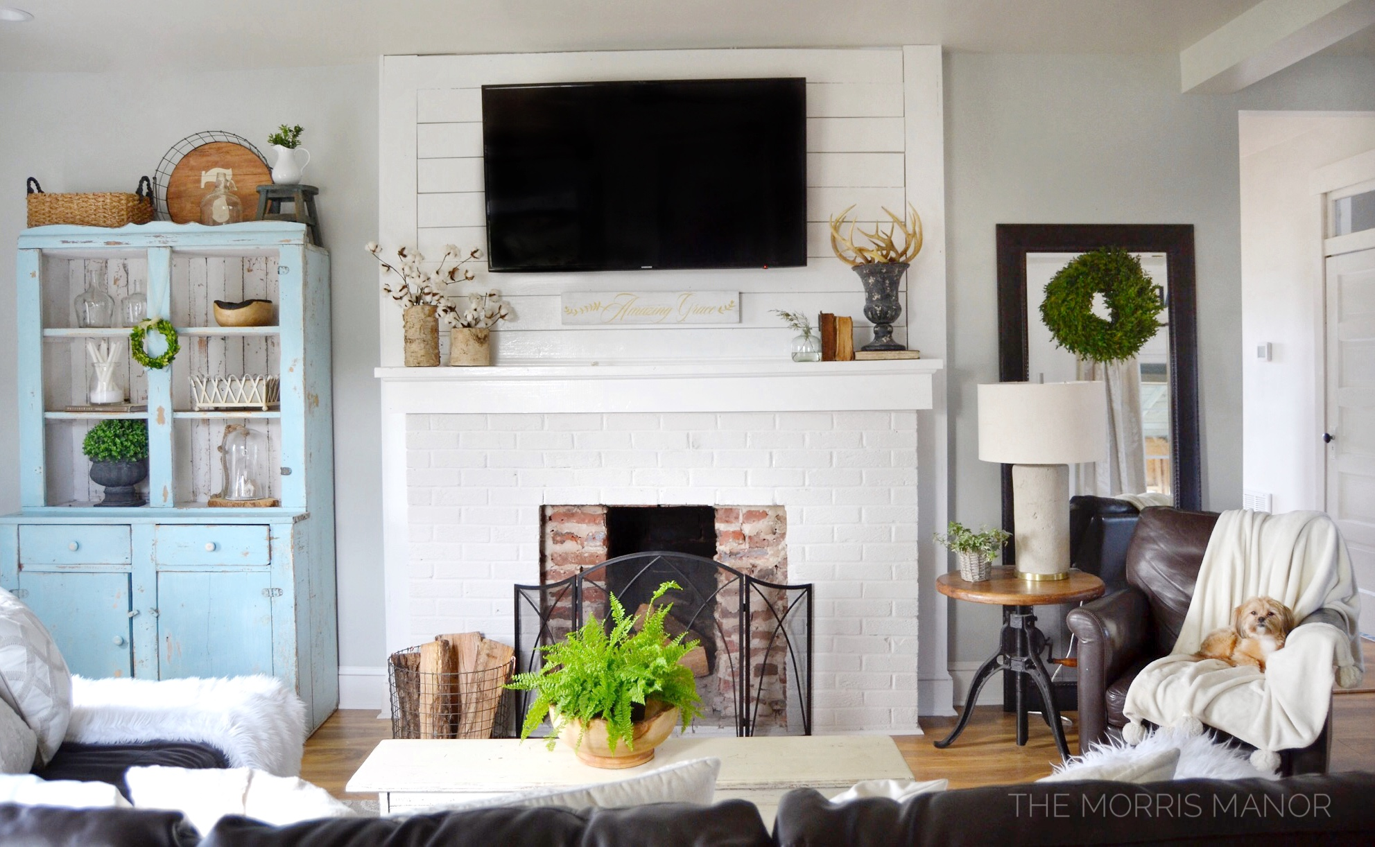 Blue vintage step back cabinet, fireplace, family room - The Morris Manor Farmhouse Home Tour